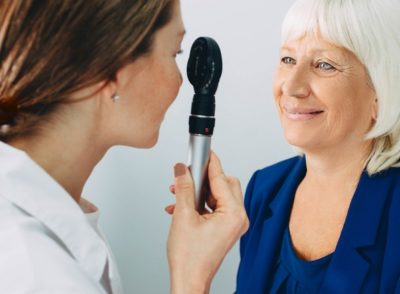 doctor examining old woman's eye with ophthalmoscope at clinic